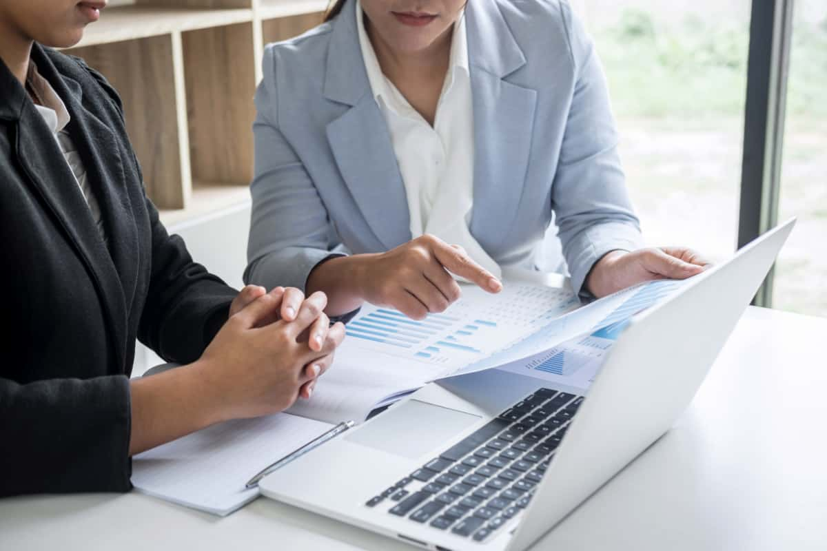 Two business women at table looking at paper charts and laptop